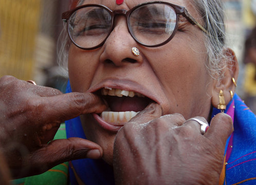 Ramjee  Sao fixes the dentures on a patient at his roadside clinic in Varanasi