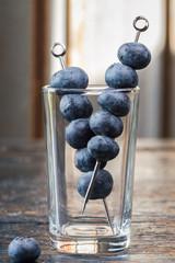 Fresh blueberries on cocktail picks in shot glass