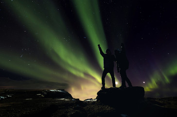 Silhouette two man standing on the rock with Aurora Borealis on the night sky, Aurora Hunting