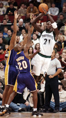 TIMBERWOLVES GARNETT PASSES OVER LAKERS PAYTON AND COOK.