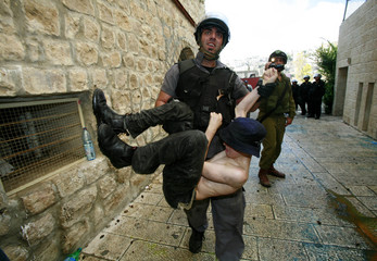 Israeli security forces restrain a settler boy in the West Bank city of Hebron