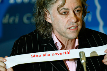 """Irish rock star Bob Geldof shows a sticker reading in Italian """"Stop poverty"""" during a news conference ..."""