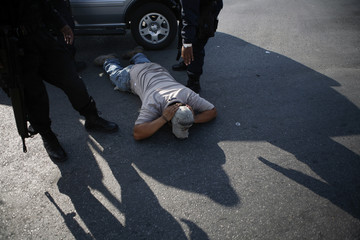 Occupant of car lies down on road as Federal policemen inspect his car during operation to break road blockade by police officers of municipality of Escobedo in Monterrey