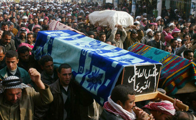 Men carry the coffins of pilgrims who where killed by gunmen attack on Wednesday during a funeral in Najaf