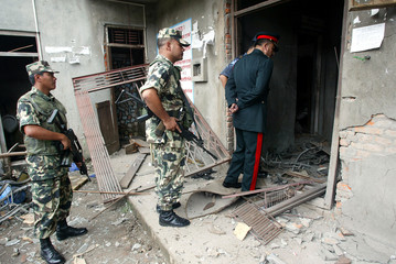 Nepalese soldiers inspect the site of a bomb blast at a government office in the Nepalese capital ...