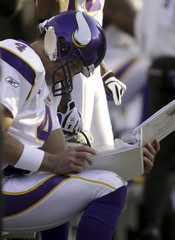 Vikings quarterback Brett Favre studies the playbook after a turnover costs the Vikings possession at Lambeau Field Green Bay