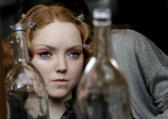 British model Lily Cole is reflected in a mirror as she gets ready before Paul Smith's Autumn/Winter 2007 show at London Fashion Week in London
