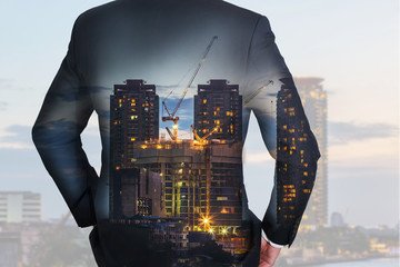 Double exposure of businessman Back, looking ahead, construction crane and building in the evening, twilight as business and vision of leader concept.