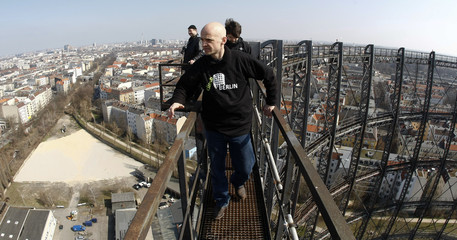 A guide tours with journalists along gangway atop of a former gas storage facility in Berlin