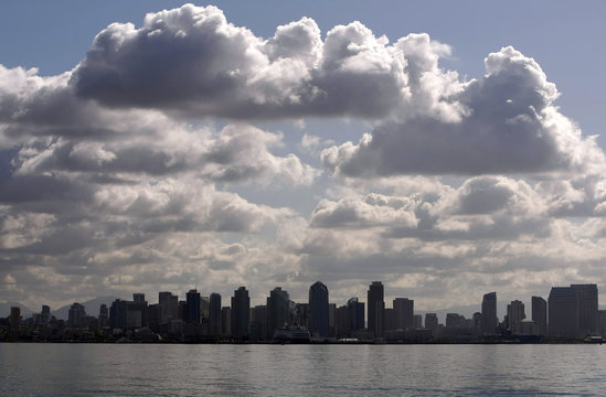 The skyline of San Diego, California is shown under blue sky and clouds