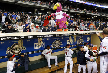 Cleveland Indians mascot Slider shares handshakes with the fans as the Indians prepare in the dugout for an American League MLB game with the Los Angeles Angels in Milwaukee