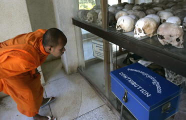 A Buddhist monk looks at a memorial stupa filled with skulls at Choeung Ek