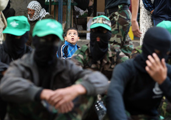 Palestinian boy sits behind Hamas militants during an anti-Israeli rally in al-Nuseirat refugee camp