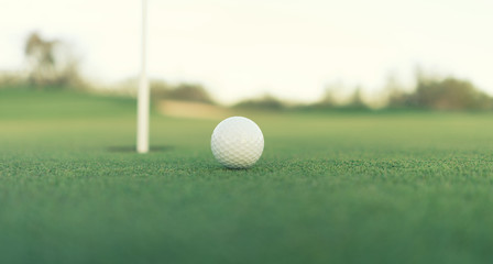 Golf ball close to hole on green