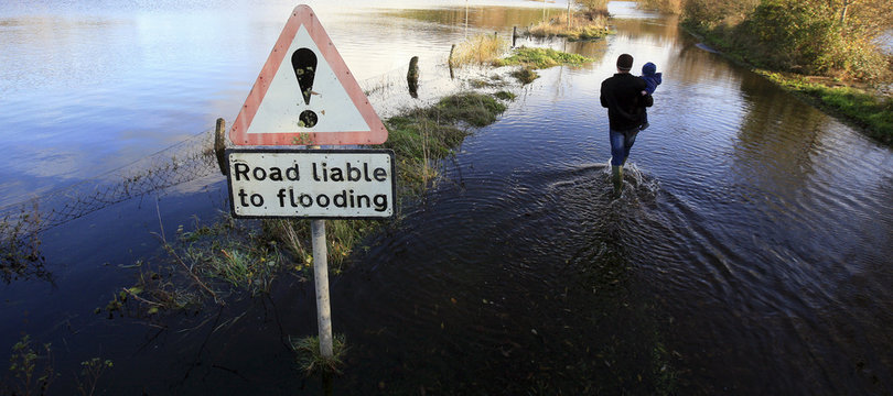 A resident of the Co.Fermanagh village of Boho makes his way to his house through flood waters in Northern Ireland