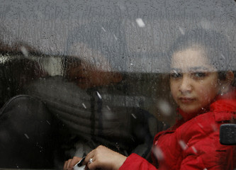 Girl looks out through the window of a vehicle during her a ride home as it snows in Damascus
