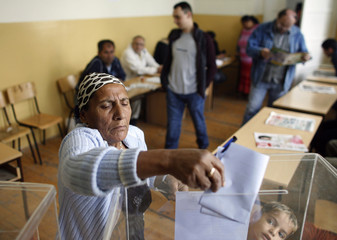 A woman casts her vote at a polling station in the northern Kosovo town of Mitrovica