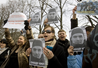 Opposition supporters shout slogans and hold portraits of detained activist Andrey Kim outside a court in Minsk