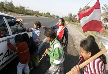 Earthquake survivors holding a Peruvian flag ask for help from a driver at the Panamerica highway near Pisco