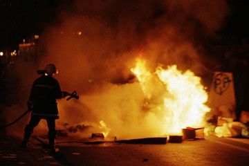 A FIREMAN PUTS OUT BURNING GARBAGE AS STREET VIOLENCE CONTINUES IN BASQUE COUNTRY.