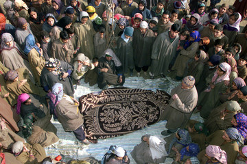KASHMIRI MUSLIM VILLAGERS GATHER AROUND THE BODY OF A WOMAN AFTER A LANDMINE EXPLOSION IN SINGHPORA.