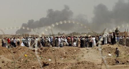 IRAQIS LINE UP OUTSIDE ABU GHRAIB PRISON NEAR BAGHDAD.