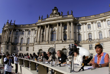 Participants of 'The Table of Free Voices' sit in front of the Humboldt University at the historic Bebelplatz square in Berlin