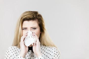 Woman being sick having flu sneeze into tissue
