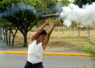 Student fires home-made mortar while they clash with riot police during protest in Managua
