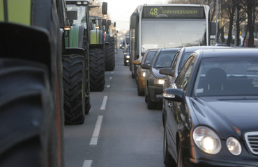 Passenger cars wait in line as farmers with their tractors block main street of  capital Riga