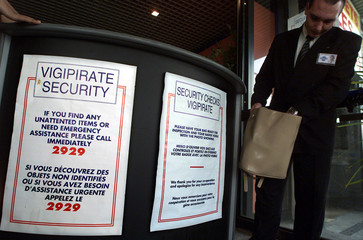 A security guard checks a bag at the entrance of the MIPCOM near signs in French and English which w..
