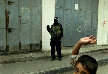 A MEMBER OF THE AL-AQSA BRIGADE STANDS IN THE STREETS OF BORAGE REFUGEECAMP PRIOR TO A DEMONSTRATION.