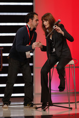 France's First Lady Carla Bruni-Sarkozy talks with a technician on stage during the 22nd Telethon in Paris