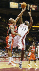 Bobcats Bogans attempts to block a shot by Cavaliers James.