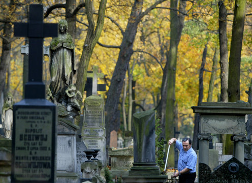 Polish man brushes leaves from the grave of his relatives at Warsaw's historic Powaski cemetery.