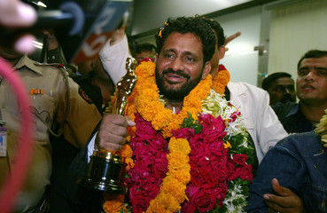 Resul Pookutty holds his Oscar award trophy as he speaks with media after arriving at the international airport in Mumbai