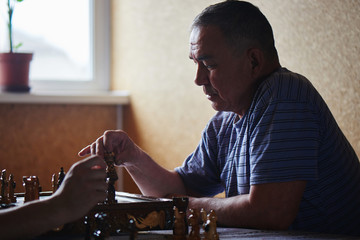 Two Kazakhs, father and son play chess