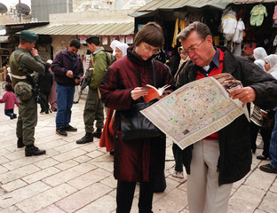TOURISTS LOOK AT OLD CITY MAP AS ISRAELI BORDER POLICE CHECK PALESTINIANS IDENTITY.
