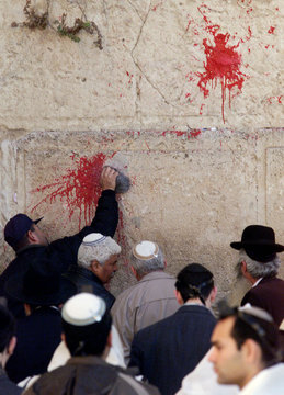 An Israeli man tries to clean a paint splat on the Western Wall, Judaism's holiest site, in Jerusale..