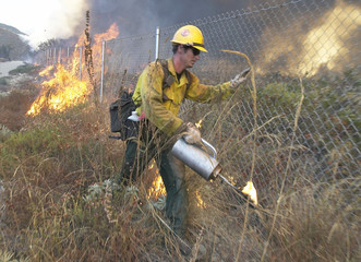 FIREFIGHTER LIGHTS BACK FIRES TO SLOW FLAMES IN RANCHO CUCAMONGA FIRE.