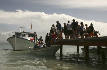 Foreign tourists embark onto a boat to see Humpback whales at the end of the season in Samana Bay in Dominican Republic