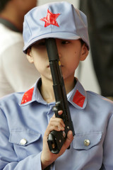 A boy dressed up as a traditional Chinese soldier holds a toy hand gun during The China International Cartoon and Animation Festival in Hangzhou