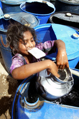 Sahin, a 6-year-old child, lifts water from a barrel with a metal pitcher while clenching her permit ...