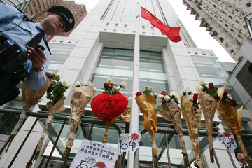 A policeman walks past bundles of rose attached outside the Liaison Office of the Central People's Government of China in Hong Kong