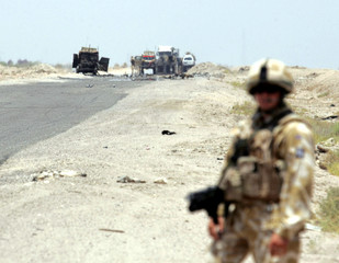 British soldier stands guard after roadside bomb attack targeting their patrol in Basra south of Baghdad