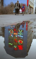 The light sculpture 'Wild Nature' by German artist Dott is reflected in a puddle.
