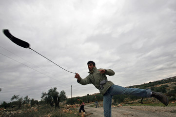 A Palestinian demonstrator throws a stone at Israeli troops in Bilin