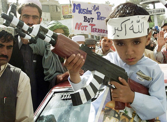 PAKISTANI MUSLIM BOY HOLDS A TOY GUN DURING AN ANTI-WAR RALLY INQUETTA.