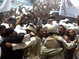SHI'ITE MUSLIM PROTESTERS CHANT SLOGANS IN FRONT OF LINE OF U.S. TROOPSDURING DEMOSTRATION IN NAJAF.