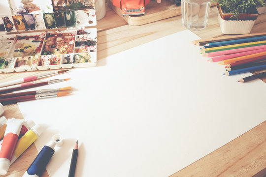 Hero Header Concept a desk of artist color pencils and paper on wood table with vintage tone